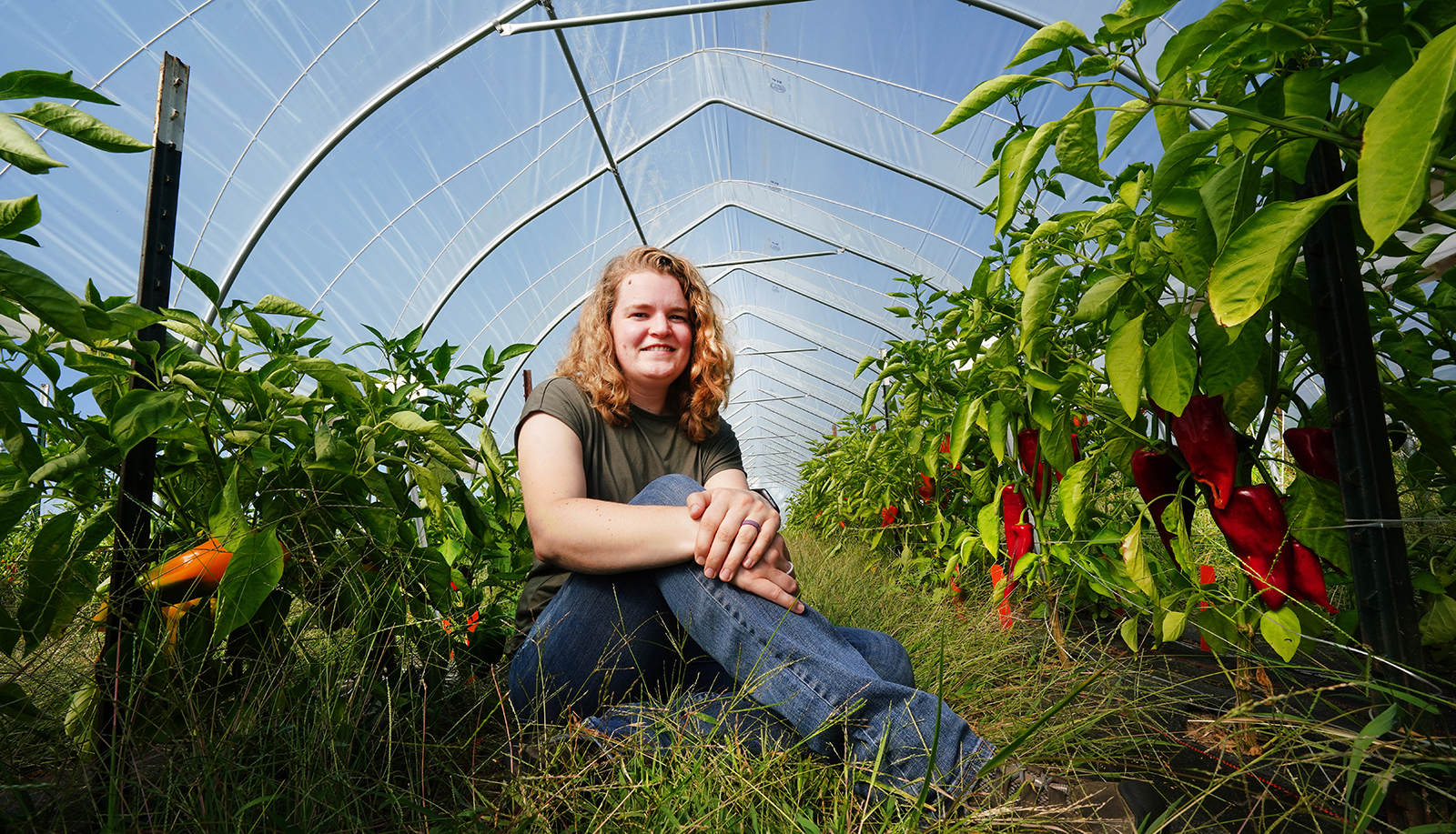 Ashley Adair sits in a greenhouse with organic peppers.